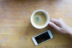 Remettez tenir le café d'expresso dans la tasse blanche avec le téléphone intelligent et copiez l'espace Photographie stock libre de droits