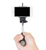 Remettez tenir le chemin de coupure blanc d'isolement par bâton de selfie Photographie stock