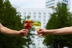 Remettez tenir le cocktail en verre tintant ensemble à extérieur photos libres de droits