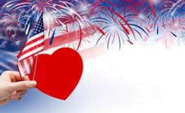 Remettez tenir le coeur de papier rouge et le drapeau des Etats-Unis avec des feux d'artifice Photo libre de droits
