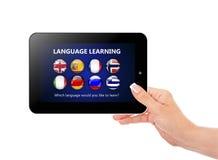 Remettez tenir le comprimé avec la page de connaissance des langues au-dessus du blanc Image libre de droits