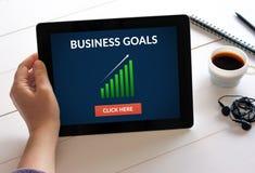 Remettez tenir le comprimé avec le concept de buts d'affaires sur l'écran Photo stock