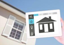 Remettez tenir le comprimé numérique avec des icônes de sécurité à la maison Image stock