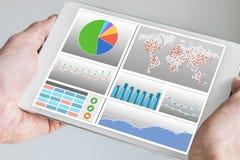 Remettez tenir le comprimé ou le périphérique mobile moderne avec le tableau de bord d'analytics Photo stock