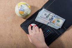Remettez tenir le conservateur de vie près des billets de banque du dollar, calculatrice photo stock