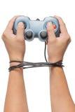 Remettez tenir le contrôleur de jeu et attaché avec des câbles d'isolement dessus Photos stock