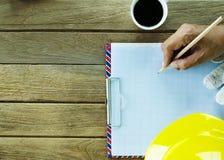 Remettez tenir le crayon sur la feuille de papier de graphique avec le casque de sécurité sur W image libre de droits