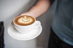 Remettez tenir le latte ou le cappuccino avec la mousse ?cumeuse, vue sup?rieure de tasse de caf? en caf? images stock