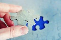Remettez tenir le morceau de puzzle avec le dernier morceau absent Photo stock