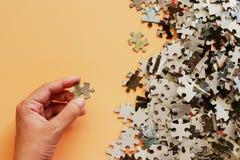 Remettez tenir le morceau de puzzle denteux sur le fond beige de couleur images stock
