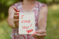 Remettez tenir le papier blanc de coeur avec je t'aime le texte sur le gree de tache floue Photos stock