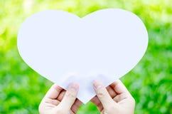 Remettez tenir le papier blanc de coeur sur le fond d'herbe de tache floue Photographie stock libre de droits