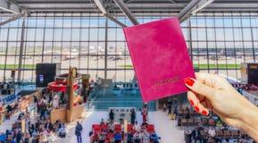 Remettez tenir le passeport générique avec le salon de attente d'aéroport occupé Image stock