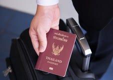 Remettez tenir le passeport thaïlandais, prêt à voyager Photo stock