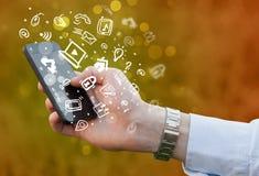 Remettez tenir le smartphone avec des icônes et le symbole de media Photographie stock libre de droits