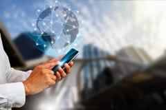 Remettez tenir le smartphone avec le globe et les connexions numériques sur le fond brouillé de ville Image stock