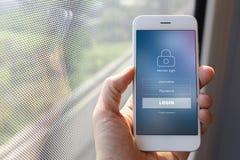 Remettez tenir le smartphone avec l'écran loging de membre sur le windo de train images stock