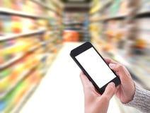 Remettez tenir le smartphone avec l'écran vide dans le supermarché de nourriture Image libre de droits