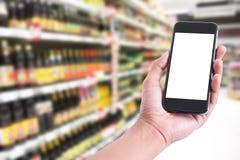 Remettez tenir le smartphone avec l'écran vide dans le supermarché de nourriture Images libres de droits