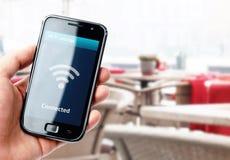 Remettez tenir le smartphone avec la connexion de Wi-Fi en café Photographie stock