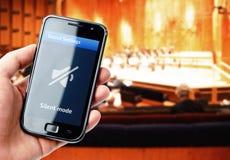 Remettez tenir le smartphone avec le bruit muet pendant le concert Images stock