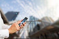Remettez tenir le smartphone avec les connexions numériques de polygone sur le fond brouillé de ville Image libre de droits
