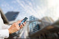 Remettez tenir le smartphone avec les connexions numériques de polygone sur le fond brouillé de ville Images stock