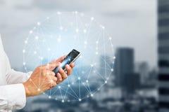 Remettez tenir le smartphone avec les connexions numériques sur le fond brouillé de ville Photos libres de droits