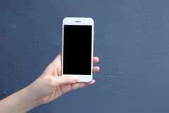 Remettez tenir le smartphone de maquette avec le fond bleu de couleur Photographie stock libre de droits