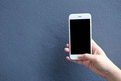 Remettez tenir le smartphone de maquette avec le fond bleu de couleur Image stock
