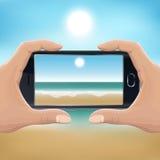 Remettez tenir le smartphone et prendre la photo de la plage Images stock