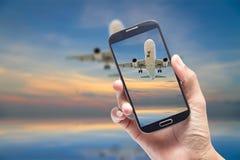 Remettez tenir le smartphone et prenez la photo du vol d'avion de vue Photo libre de droits