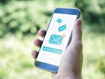 Remettez tenir le smartphone mobile avec l'icône de message sur un écran Graphisme d'email photo stock
