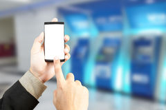 Remettez tenir le smartphone pour des opérations bancaires de transfert avec le backgroun de tache floue photographie stock