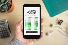 Remettez tenir le téléphone intelligent avec le concept en ligne de billets sur l'écran photo stock