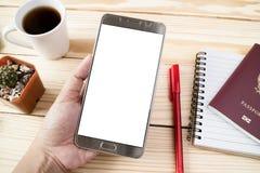 Remettez tenir le téléphone intelligent avec du café sur le fond en bois Photo libre de droits
