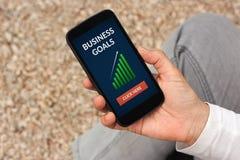 Remettez tenir le téléphone intelligent avec le concept de buts d'affaires sur l'écran Images libres de droits