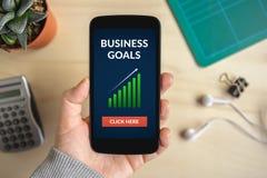 Remettez tenir le téléphone intelligent avec le concept de buts d'affaires sur l'écran Images stock