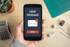 Remettez tenir le téléphone intelligent avec le nouveau concept de message sur l'écran images libres de droits