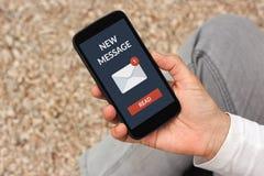 Remettez tenir le téléphone intelligent avec le nouveau concept de message sur l'écran images stock