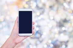 Remettez tenir le téléphone intelligent avec les cercles colorés du Ba léger de bokeh Photographie stock libre de droits