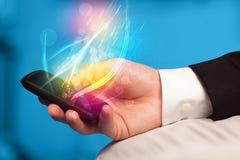 Remettez tenir le téléphone intelligent avec les lignes rougeoyantes abstraites Photo stock