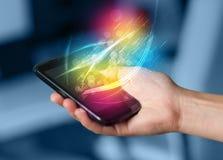 Remettez tenir le téléphone intelligent avec les lignes rougeoyantes abstraites Photos stock
