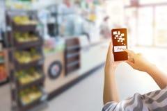 Remettez tenir le téléphone intelligent et indiquer l'index plus fin le bouton de salaire photo stock
