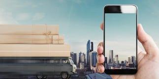 Remettez tenir le téléphone intelligent mobile écran vide, et le fourgon de livraison avec des boîtes de colis sur le toit condui image stock