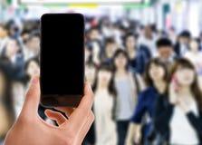 Remettez tenir le téléphone intelligent mobile avec l'écran noir avec une foule des personnes en Asie sur le fond photographie stock