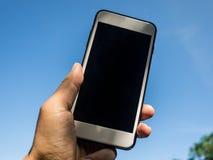 Remettez tenir le téléphone intelligent mobile avec le fond de ciel Images libres de droits