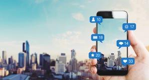 Remettez tenir le téléphone intelligent mobile, avec les icônes d'avis et le fond de ville images libres de droits