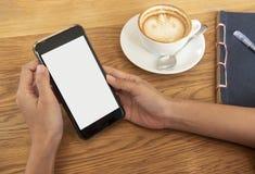 Remettez tenir le téléphone portable avec l'écran blanc vide en café Images stock