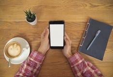 Remettez tenir le téléphone portable avec l'écran blanc vide en café Photographie stock